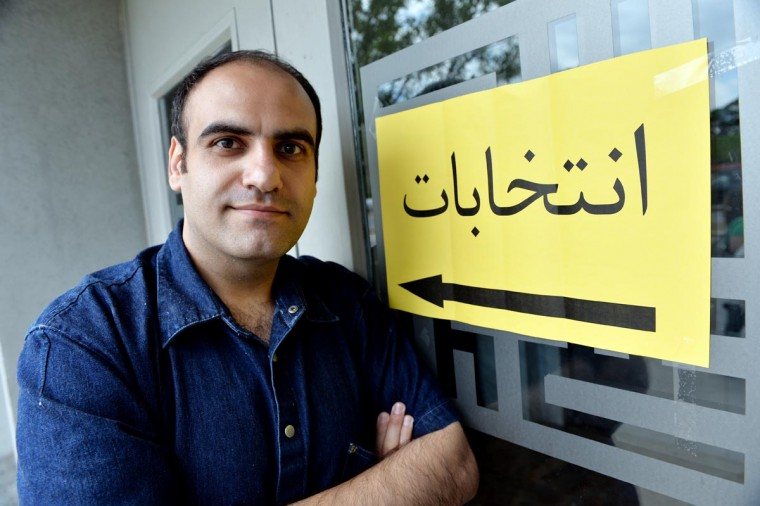 "Ghassem Tofighi, a Ph.D student at Ryerson University in Toronto, poses next to a sign that says ""entekhabat"" in Farsi or ""election"" in English after he voted for president of Iran June 14, 2013 at the Islamic Cultural Center of New York in the Queens borough of New York. Tofighi took a bus from Toronto to New York to vote since there were no polling places in Canada for the Iranian election. (Stan Honda/AFP/Getty Images)"