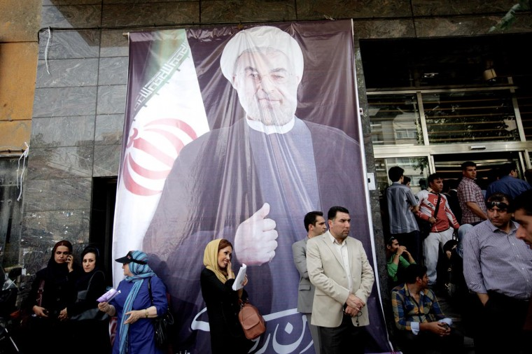 Iranians gather under a giant portrait of moderate presidential candidate, Hassan Rowhani outside his campaign headquarters in downtown Tehran on June 15, 2013. (Behrouz Behri/AFP/Getty Images)