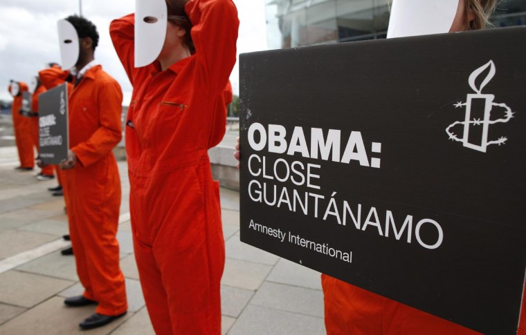 Amnesty International volunteers wear masks and orange suits depicting detainees at Guantanamo Bay during a photo call calling on U.S. President Barrack Obama to close the Guantanamo Bay military detention camp outside the Waterfront Hall in Belfast, Northern Ireland, on June 16, 2013 ahead of the G8 Summit. (Peter Muhly/AFP/Getty Images)