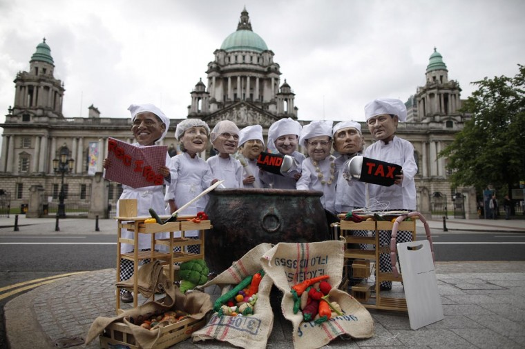 Oxfam charity volunteers wear masks depicting the G8 leaders around a large cauldron during a photo call to draw attention to the issue of world hunger outside City Hall in Belfast, Northern Ireland, on June 16, 2013. (Peter Muhly/AFP/Getty Images)