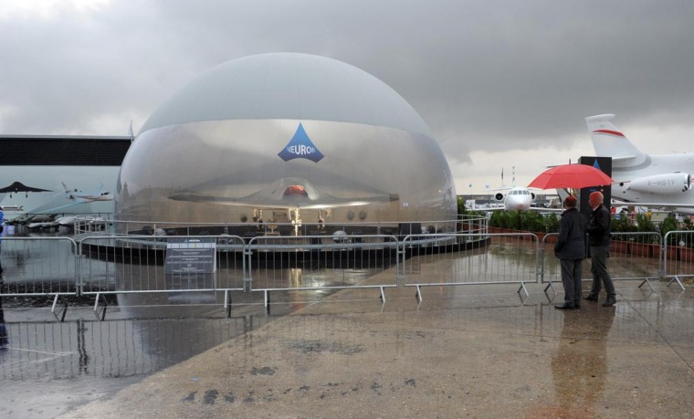 "Visitors looks at the ""Neuron"" military drone on the Dassault pavilion as heavy rain falls at Le Bourget airport on June 17, 2013 on the opening day of the International Paris Air show. (Eric Piermont/AFP/Getty Images)"