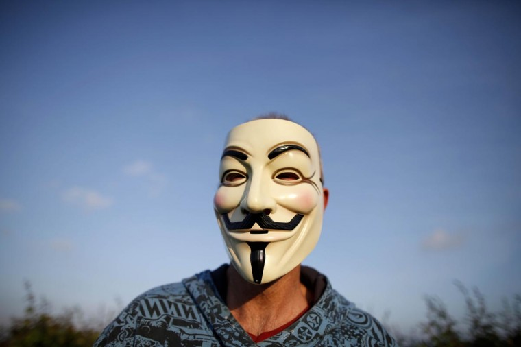 A protester wears a mask at the fence near the G8 Summit at Lough Erne Resort in Enniskillenin Northern Ireland on June 17, 2013. (Peter Muhly/AFP/Getty Images)