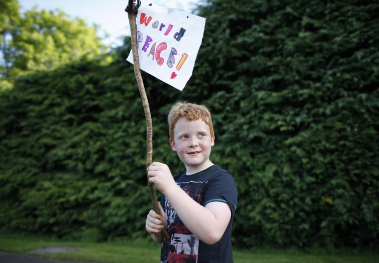 Joe Shannon, 6 years old holds a sign saying 'World Peace' as Protesters march to the G8 Summit at Lough Erne Resort in Enniskillen, Northern Ireland on June 17, 2013. (Peter Muhly/AFP/Getty Images)