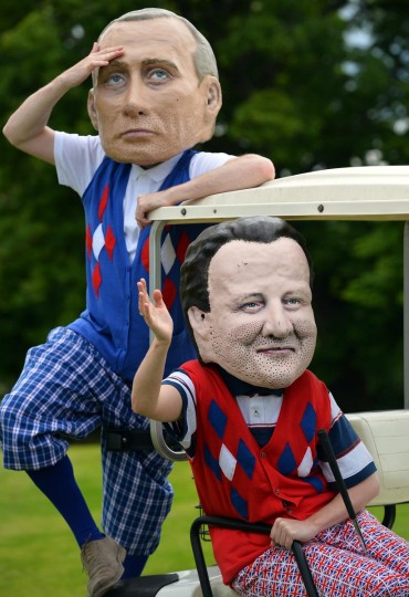 Protesters from anti-hunger charity Oxfam wearing masks depicting Russia's President Vladimir Putin (L) and Britain's Prime Minister David Cameron pose on a golf course in Enniskillen in Northern Ireland on June 18, 2013 near the venue of the G8 summit at the golfing resort of Lough Erne. (Paul Ellis/AFP/Getty Images)