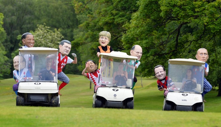 Protesters from anti-hunger charity Oxfam wearing masks depicting leaders of G8 countries pose on a golf course in Enniskillen in Northern Ireland on June 18, 2013. (Paul Ellis/AFP/Getty Images)