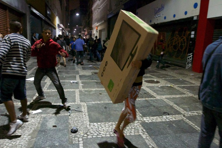 Unidentified people carry a tv set during clashes in Sao Paulo, Brazil on June 18, 2013 against a recent rise in public bus and subway fare from 3 to 3.20 reais (1.50 USD). (Daniel Guimaraens/AFP/Getty Images)