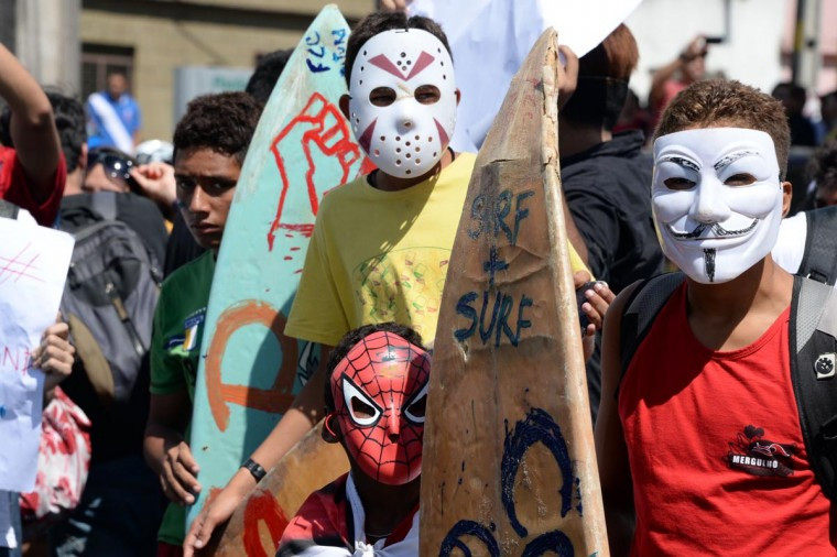 Young surfers wearing masks march in Fortaleza, Northern Brazil, on June 19, 2013 during a protest of what is now called the 'Tropical Spring' against corruption and price hikes. (Vanderlei Almeida/AFP/Getty Images)
