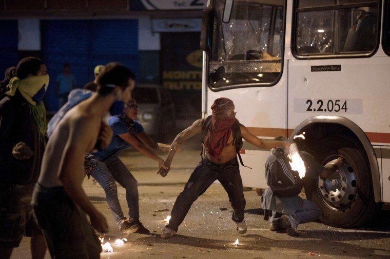 A protester tries to prevent another demonstrator from setting a bus on fire late on June 19, 2013 during clashes in the center of Niteroi, 10 kms from Rio de Janeiro. (Christophe Simon/AFP/Getty Images)