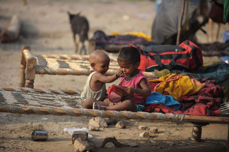 Indian children, who were evacuvated due to rising waters, sit outside makeshift shelters on the banks of the Yamuna River in New Delhi. Nearly 5,000 people in the city have been evacuated from low-lying areas like Usmanpur, Yamuna Bazar, Bhajanpura, Shastri Park and Tibetan Market, and shifted to over 900 relief camps set up by the city government. (Noah Seelam/AFP/Getty Images)
