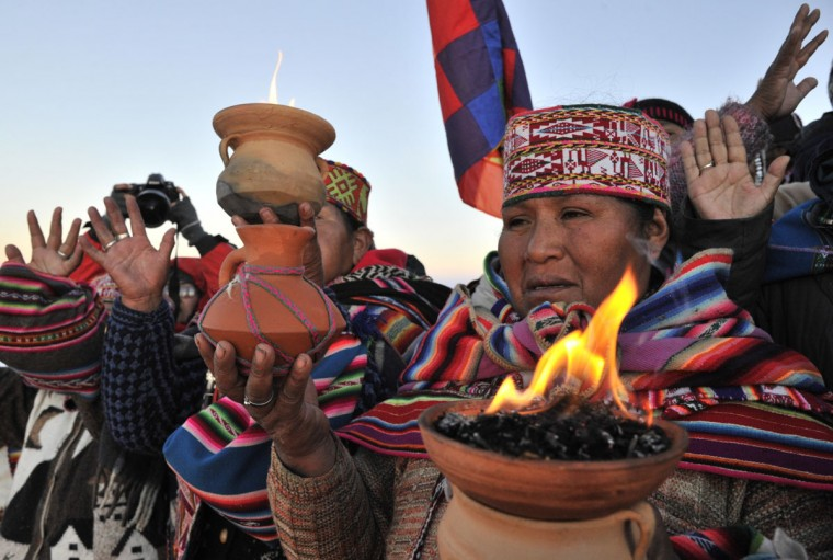 Aymara priests perform a ritual at sunrise to celebrate the Aymara New Year on June 21, 2013 at the Uyuni salt flat in Bolivia. A crowd gathered to receive the first rays of Tata Inti (god Sun) during the celebration of the winter solstice that marks the beginning of the 5521st year in the Aymara calendar. (Aizar Raldes/AFP/Getty Images)