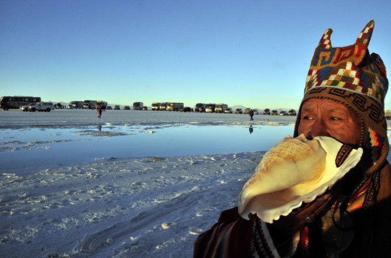 """An Aymara priest blows a """"pututu"""" (a traditional wind instrument made with the horn of an ox or a conch) during a ritual at sunrise to celebrate the Aymara New Year on June 21, 2013 at the Uyuni salt flat in Bolivia. A crowd gathered to receive the first rays of Tata Inti (god Sun) during the celebration of the winter solstice that marks the beginning of the 5521st year in the Aymara calendar. (Aizar Raldes/AFP/Getty Images)"""