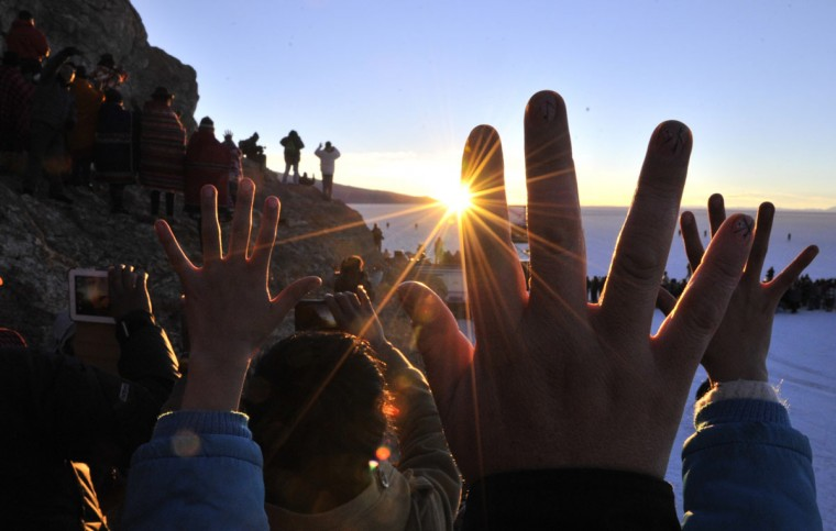 People raise their hands during a ritual at sunrise to celebrate the Aymara New Year on June 21, 2013 at the Uyuni salt flat in Bolivia. A crowd gathered to receive the first rays of Tata Inti (god Sun) during the celebration of the winter solstice that marks the beginning of the 5521st year in the Aymara calendar. (Aizar Raldes/AFP/Getty Images)