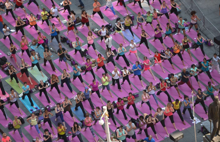 Participants practice yoga as part of a series of mass yoga classes set on Times Square to celebrate the summer solstice, in New York. (Emmanuel Dunand/AFP/Getty Images)