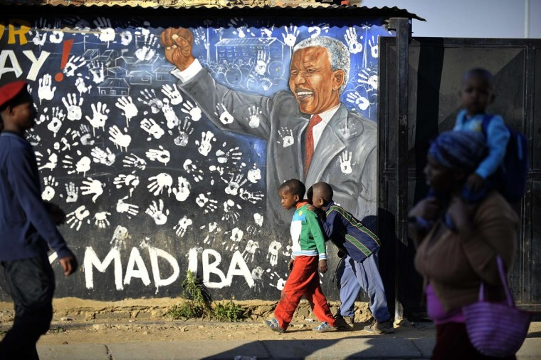 Young Alexandra's residents play near a panting of anti-apartheid icon Nelson Mandela in Soweto, where Mandela once lived, on June 24, 2013. A statement issued by the South African government reported that former South African president Nelson Mandela's health was in a critical stage after his condition in hospital worsened over the course of 24 hours. Alexander Joe/AFP/Getty Images)