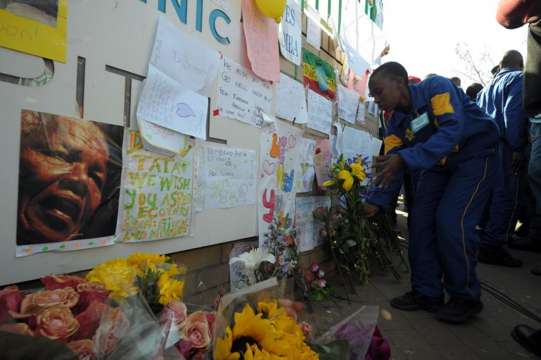 One of 37 police officers places flowers for former South African President Nelson Mandela on June 25, 2013 outside the Mediclinic heart hospital in Pretoria, where the former anti-apartheid leader spent a second night in critical condition. (Alexander Joe/AFP/Getty Images)