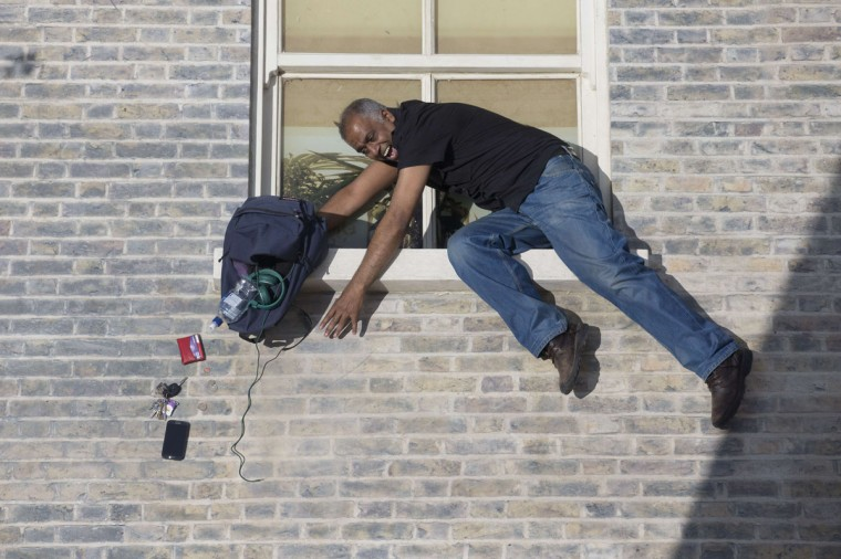 "A man interacts with a large-scale installation art piece by Argentinian artist Leandro Erlich, entitled ""Dalston House,"" in East London on June 25, 2013. (Justin Tallis/AFP/Getty Images)"