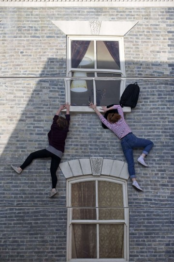 "People interact with a large-scale installation art piece by Argentinian artist Leandro Erlich, entitled ""Dalston House,"" in East London on June 25, 2013. (Justin Tallis/AFP/Getty Images)"