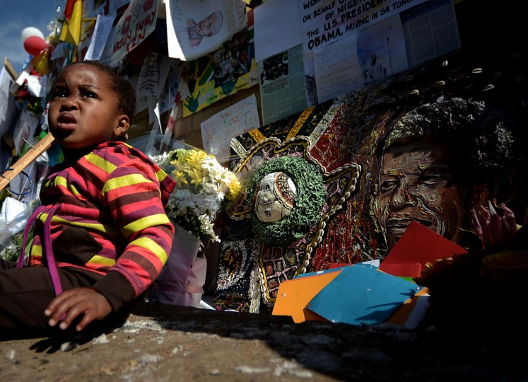 "A baby sits by messages and flowers left for former South African President Nelson Mandela outside the MediClinic Heart hospital in Pretoria where Mandela is hospitalized. U.S. President Barack Obama Saturday decided not to visit Mandela in the hospital to preserve the ""peace and comfort"" of the anti-apartheid legend, whose family he met with instead. (Filippo Monteforte/AFP/Getty Images)"
