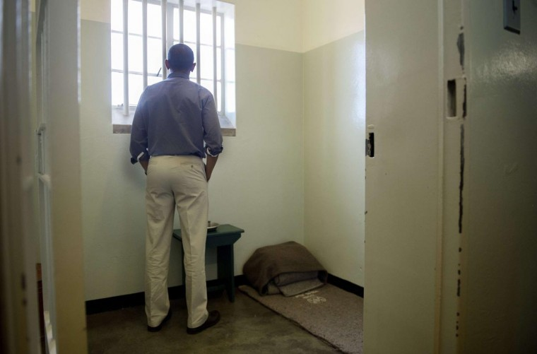 President Barack Obama looks out the window from the cell where Nelson Mandela, an anti-apartheid legend, was once jailed on Robben Island, on June 30, 2013. Paying homage to the 94-year-old former South-African president, who is critically ill in hospital, Obama stared into the stark cell where Mandela spent two thirds of his 27 years in jail. (Jim Watson/AFP/Getty Images)