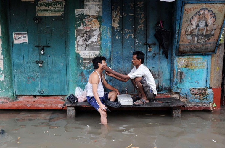A barber shaves a customer in his temporary shop alongside a water-logged street in Kolkata on June 30, 2013. Heavy rains in various parts of Kolkata have disrupted normal life as several parts of the city became waterlogged and trains services were partially disrupted. (Dibyangshu Sarkar/AFP/Getty Images)