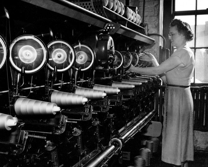 One third of a mile of thread goes into a man's suit. This machine waxes thread to make it stronger and easier to sew, then winds it on spools, 1954. (Hans Marx/Baltimore Sun)