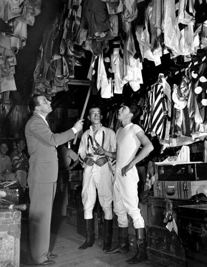 Arthur G. Snodgrass, custodian, has the task of finding the right silks for the right riders among this kaleidoscopic collection in the crowded jockey's room at the Bowie race track, 1949. (Hans Marx/Baltimore Sun)