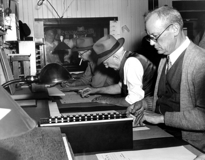 They're the Lightning Calculators Who Figure Up What Your Ticket Is Worth -- The calculators figure out, in three minutes, the prices winning horses pay at the Pimlico track, 1950. (Hans Marx/Baltimore Sun)