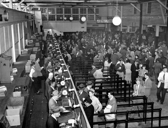 Race goers place bets at Pimlico. The ticket machines are linked to the totalisator, speeding up price calculations, 1950. (Hans Marx/Baltimore Sun)
