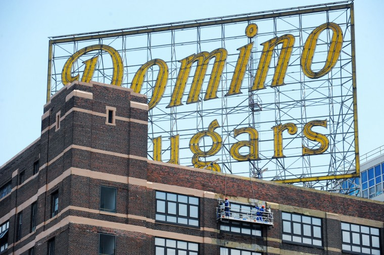 With the Domino Sugars sign looming above, workers clean the west-side exterior of the Domino plant, part of a building beautfication project that could take two years. (Kenneth K. Lam/Baltimore Sun Photo)