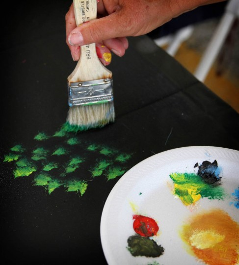 Local artist Anna Pasqualucci demonstrates how to paint trees during a screen painting workshop put on by The Painted Screen Society of Baltimore during the Maryland Folklife Festival on June 15th . (Erin Kirkland/Baltimore Sun)