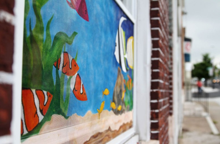 Highlandtown's painted screens aren't just for businesses and commercial properties. This under the sea themed painting is on a residential window on Eastern Ave. (Erin Kirkland/Baltimore Sun)