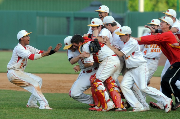 Calvert Hall's Manny Rodriguez applies the brakes as he approaches celebrating teammates after the Cardinals beat Gilman, 4-2, at Ripken Stadium in Aberdeen for their seventh MIAA A Conference championship in nine years under coach Lou Eckerl. Calvert Hall came out of the loser's bracket for the second straight year to claim the program's 30th crown since 1929. (Algerina Perna/BSMG)