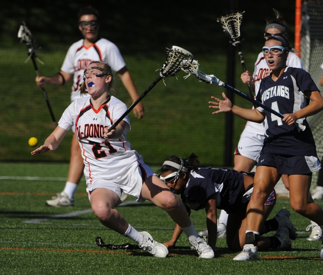 McDonogh High's #21 Olivia Jenner goes down, losing the ball , while being chased by a duo of Marriotts Ridge defenders, #4 Alexis Zadjura and #7 Caroline Corbliss. Marriotts Ridge girls took on the 87-0 McDonogh girls lacrosse team and lost 19-9, making McDonogh 88-0. (Gene Sweeney Jr./BSMG)