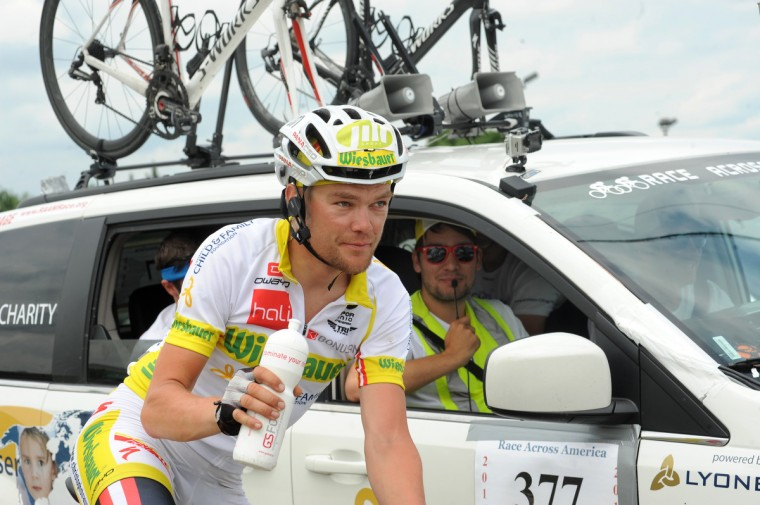 Christoph Strasser gets a drink while with his team while waiting at a red light in Laurel as he rides on the final day of his record setting Race Across America. (Jerry Jackson/Baltimore Sun)