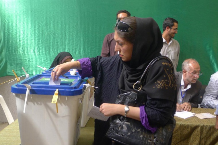 A voter drops a paper ballot in the plastic bin at the Qolhak Jame mosque in north central Tehran, Iran, during Iranian presidential elections, Friday, June 14, 2013. (Roy Gutman/MCT)