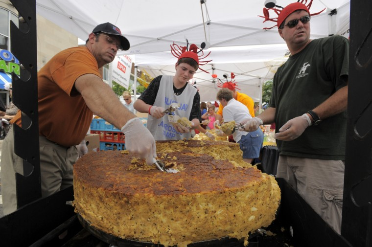 "Jim Cupp, left, Brendan Schniedwind, 14 and Steve Schwartz work together behind the counter, dipping in to the claimed ""world's biggest crab cake,"" at more than 250 pounds, selling them at $10 each at the annual 2009 Honfest in the Hampden community Saturday, June 13, 2009. (Karl Merton Ferron /Baltimore Sun)"
