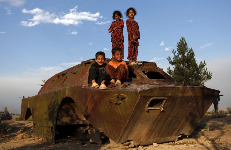Afghan children play on a destroyed armoured vehicle in Kabul June 30, 2013. (Mohammad Ismail/Reuters)