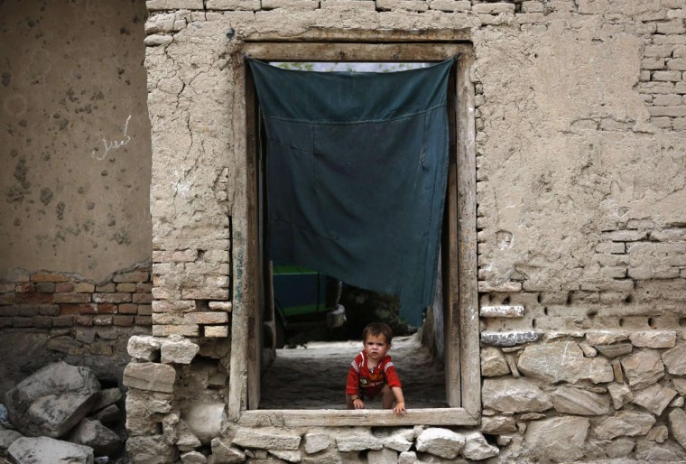 An Afghan child looks out from a door of a house in Kabul June 13, 2013. (Mohammad Ismail/Reuters)