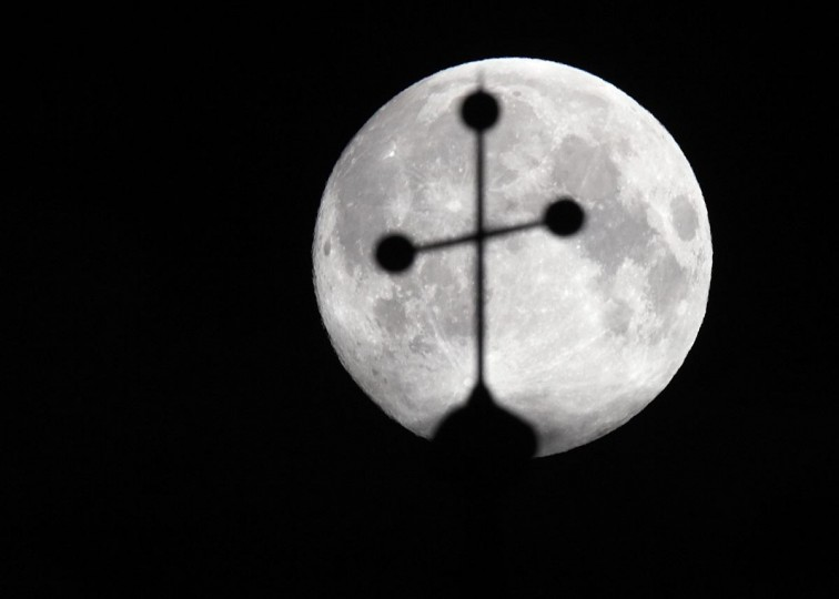 "The ""supermoon"" is pictured behind the cross of a church in Vienna June 23, 2013. (Heinz-Peter Bader/Reuters)"