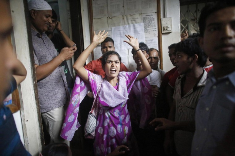 A garment worker from textile company Envoy Group shouts, while participating in a protest during a strike, in front of the factory in Dhaka June 10, 2013. The workers demanded increase in pay, money paid for work done, and a larger lunch allowance, local media reported. (Andrew Biraj/Reuters)