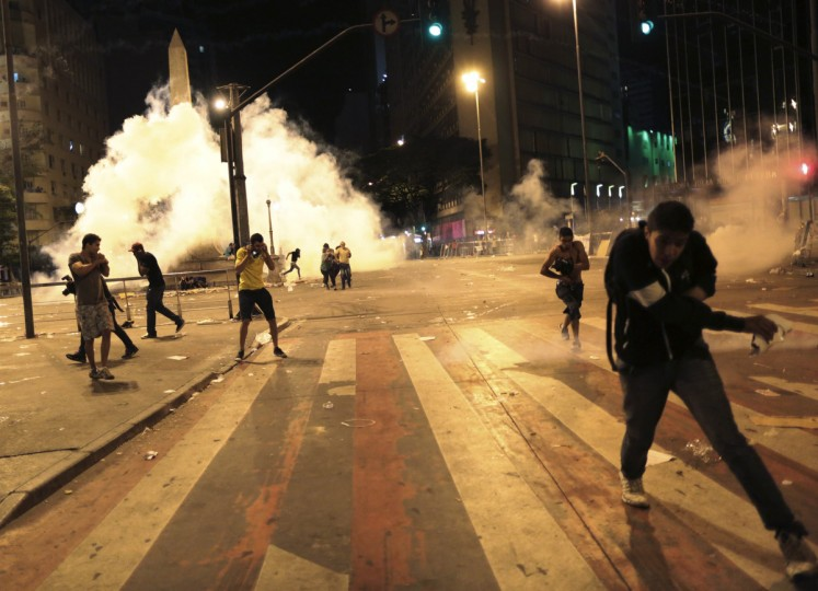 Demonstrators run as riot police fire tear gas during clashes at a protest on the streets of Belo Horizonte. Tens of thousands of Brazilians have taken to the streets this month in the biggest protests in 20 years, fueled by an array of grievances ranging from poor public services to the high cost of World Cup soccer stadiums and corruption. (Ueslei Marcelino/Reuters photo)