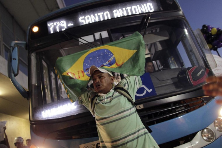 A man holding a Brazilian national flag stands in front of a bus during a protest demanding improvements be made to the public transport system, at the bus station in the centre of Brasilia June 19, 2013. (Christophe Simon/AFP/Getty Images)