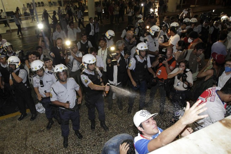 A police officer uses pepper spray on demonstrators protesting against the Confederation's Cup and the government of Brazil's President Dilma Rousseff outside the national congress in Brasilia June 17, 2013. (Ueslei Marcelino/Reuters)