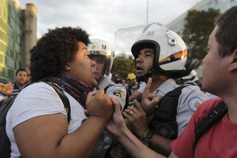 A demonstrator argues with police during a protest against the Confederation's Cup and the government of Brazil's President Dilma Rousseff in Brasilia June 17, 2013. (Ueslei Marcelino/Reuters)