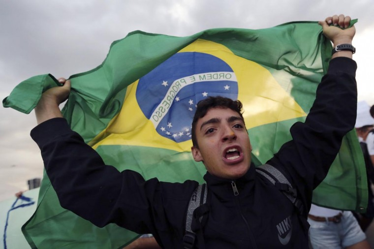 A demonstrator with the Brazilian flag protests against the Confederation's Cup and the government of Brazil's President Dilma Rousseff in Brasilia June 17, 2013. (Ueslei Marcelino/Reuters)