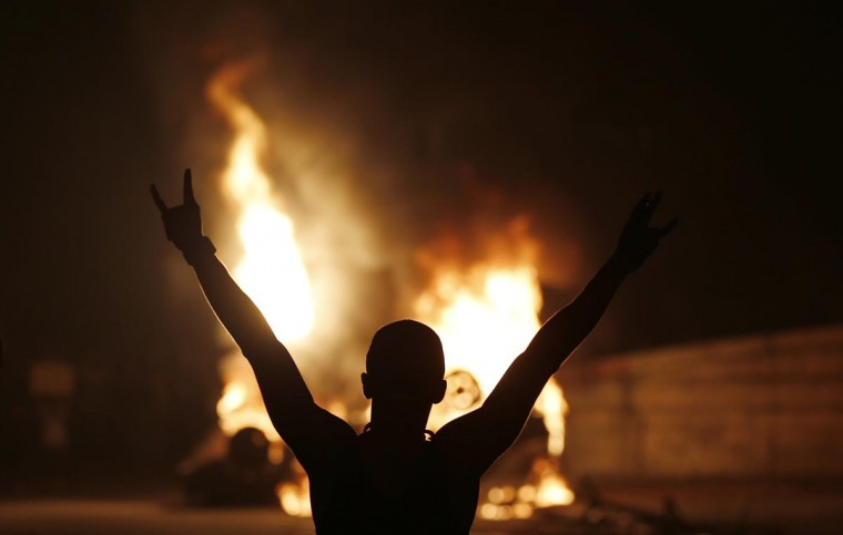 A demonstrator celebrates by a burning car in downtown Rio de Janeiro June 17, 2013. (Sergio Moraes/Reuters)