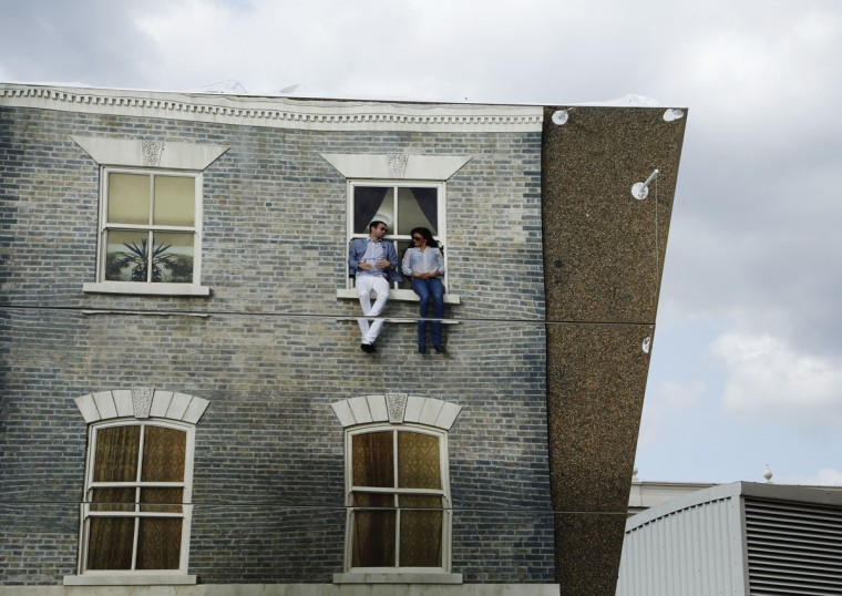 "BBC reporter Anahita Shams is seen in a reflection as she interviews Argentine artist Leonado Erlich (L) on his optical illusion installation ""Dalston House"" in east London June 25, 2013. (Luke MacGregor/Reuters)"