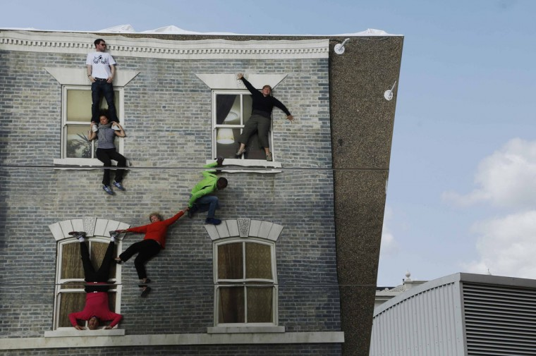 """Visitors are seen by their reflections as they pose on Argentine artist Leonardo Erlich's optical illusion installation """"Dalston House"""" in east London June 25, 2013. (Luke MacGregor/Reuters)"""