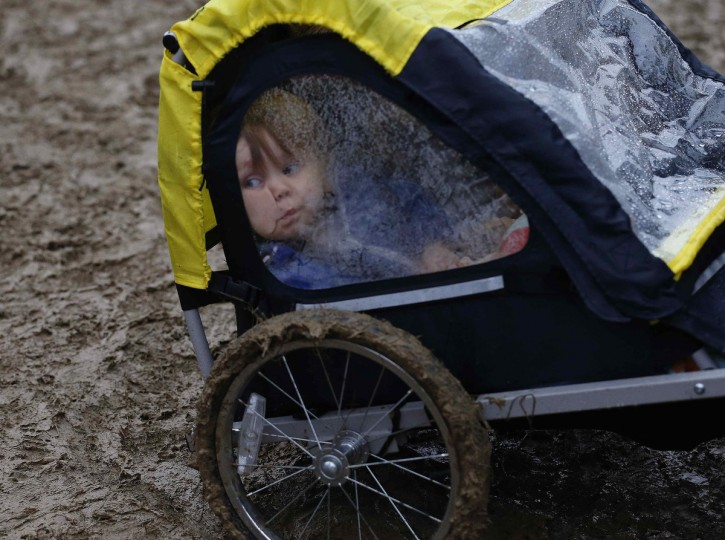 Harry, 2, is pulled through the mud on the second day of Glastonbury music festival at Worthy Farm in Somerset, June 27, 2013.(Olivia Harris/Reuters)