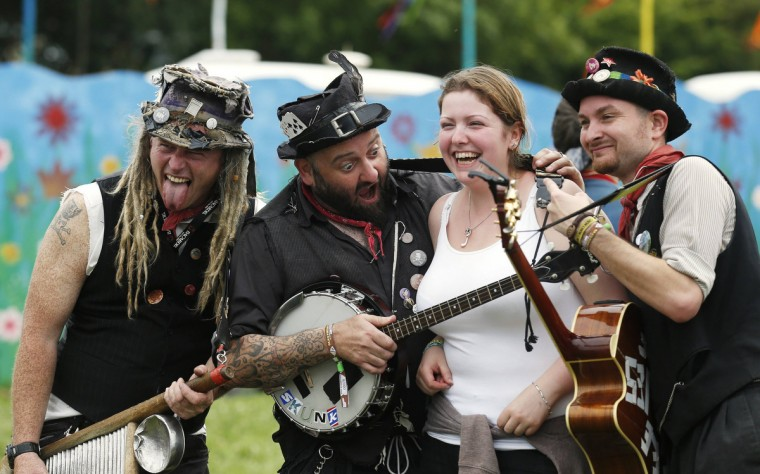 A festival goer (2nd R) poses for a photo with a folk band on the third day of Glastonbury music festival at Worthy Farm in Somerset, June 28, 2013. (Olivia Harris/Reuters)